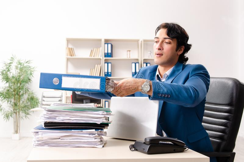 The young handsome busy employee sitting in office. Young handsome busy employee sitting in office royalty free stock photo