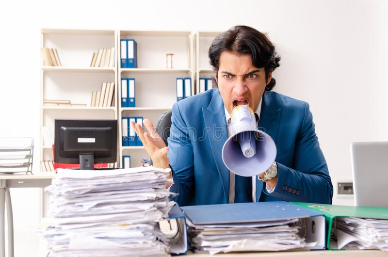 The young handsome busy employee sitting in office royalty free stock image