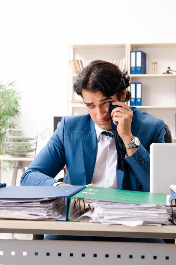 The young handsome busy employee sitting in office. Young handsome busy employee sitting in office royalty free stock image