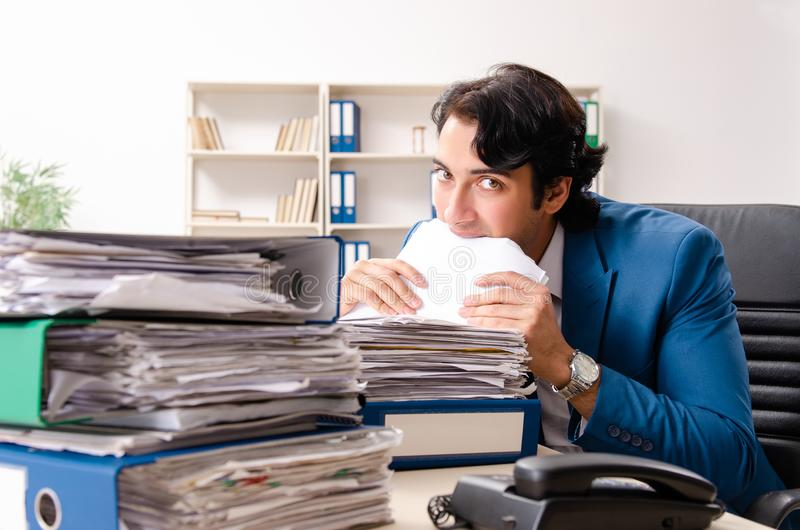 The young handsome busy employee sitting in office. Young handsome busy employee sitting in office royalty free stock photos