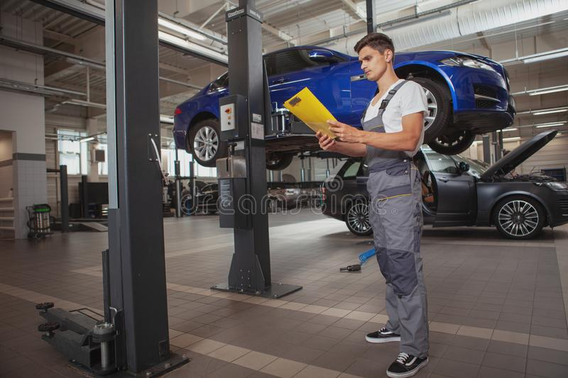 Young handsome car mechanic repairing vehicle in his garage royalty free stock photo