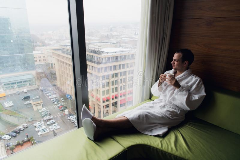 Young handsome carefree man near modern full length window enjoying a cup of coffee while looking outside, good morning royalty free stock images