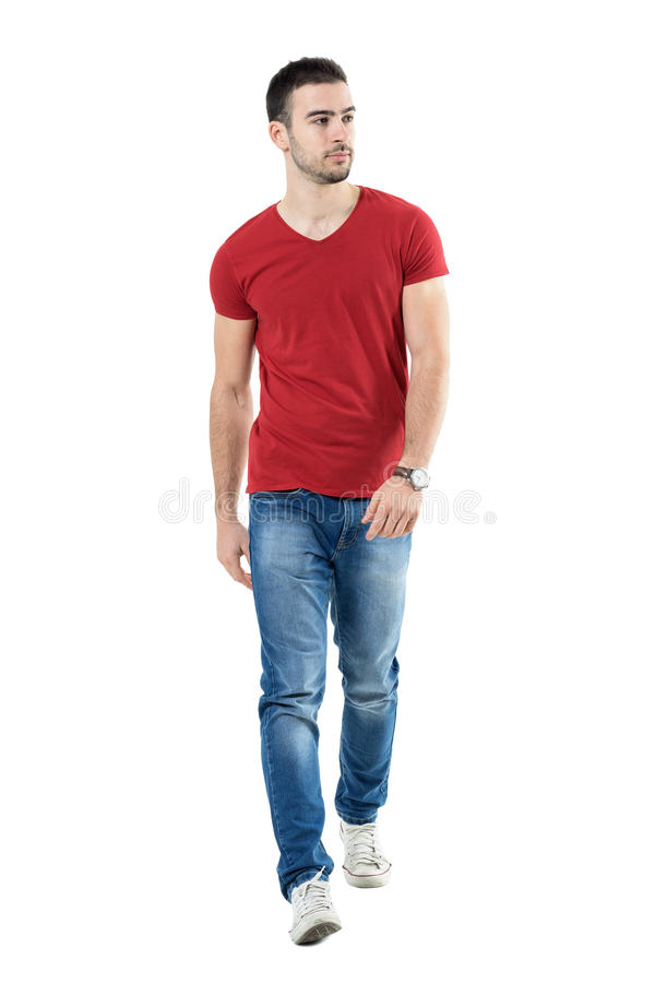 Young handsome casual man walk towards camera looking away. Full body length portrait isolated over white studio background royalty free stock images