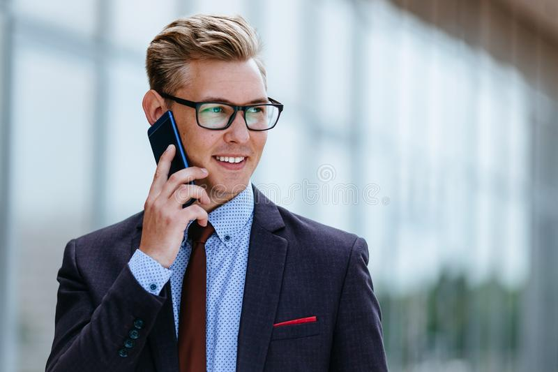 Young handsome Caucasian businessman in glasses talking on mobile phone in front of office building. Male executive royalty free stock photo
