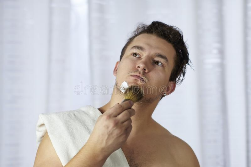 Young handsome caucasian man begins to shave with brush and foam, vintage style of old barber. Thoughtful serious look royalty free stock images