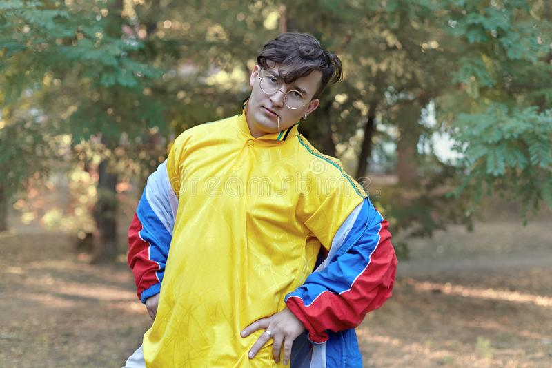 Young handsome caucasian man with bright freaky sportswear 70s style stands at a morning park. Stick in the mouth, golden glasses,. Earring and ring royalty free stock image
