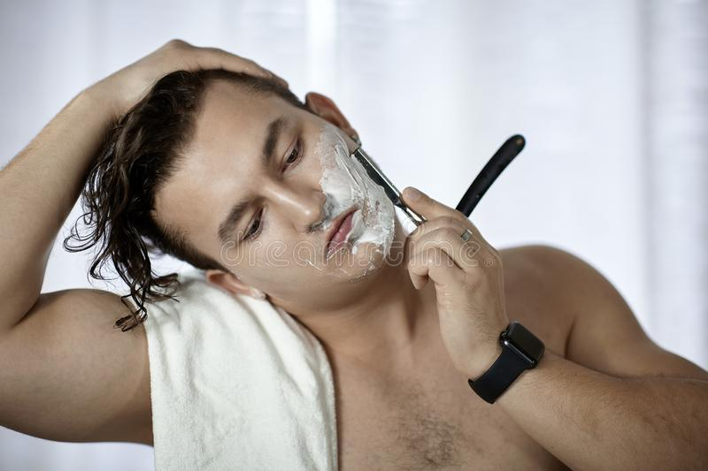 Young handsome caucasian man with electronic watch on wrist shaves with straight razor vintage style of old barbership. Thoughtf stock image