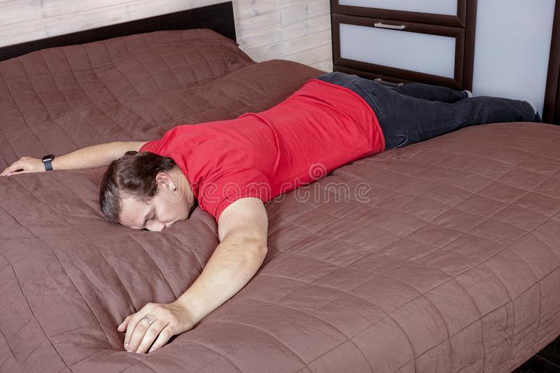 Young handsome caucasian man lies on a bed with face down, deeply sleeping, drunk, or exhausted. royalty free stock photo