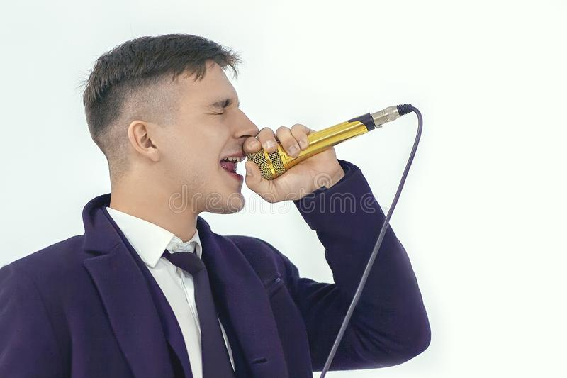 Young handsome caucasian man sings into golden microphone with closed eyes and passion. Concept of party or karaore vocal. royalty free stock images