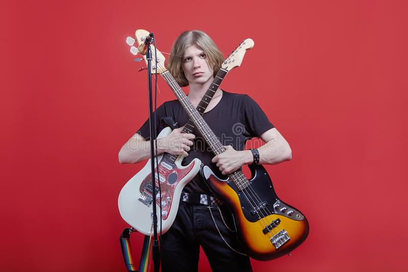 Young handsome caucasian man stands with two guitar, acoustic and electric ones in front of the stack with microphone. Musician po royalty free stock photos