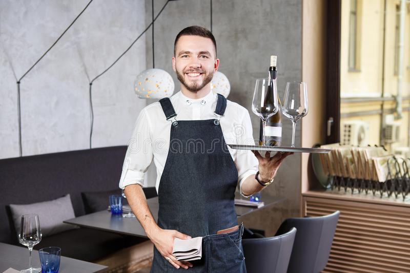 A young, handsome Caucasian waiter stands in the interior of the restaurant with a tray in his hand, two glasses and a roll of win royalty free stock images
