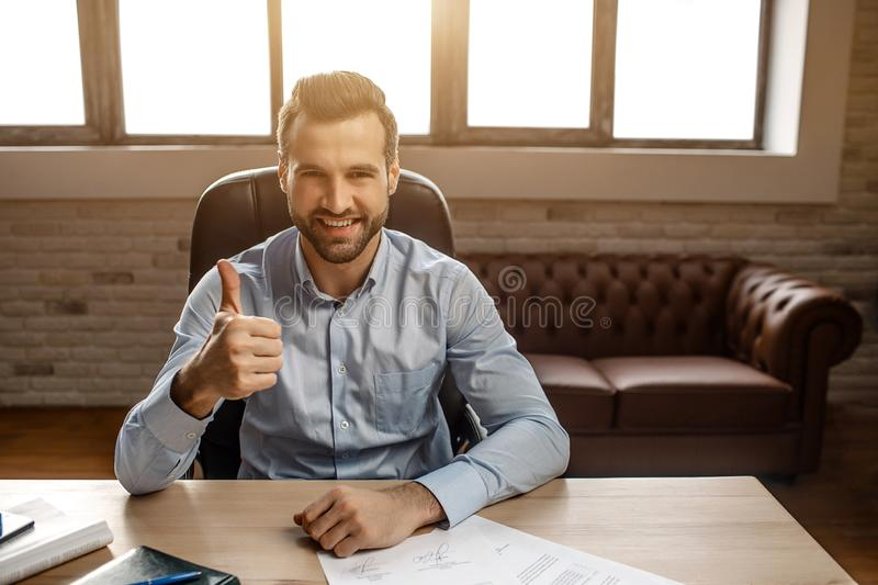 Young handsome cheerful businessman sit on table and pose in his own office. He hold big thumb up and smile. Nice happy royalty free stock photography