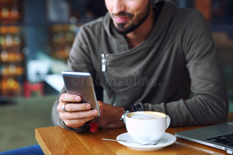 Young handsome cheerful hipster guy at the restaurant using a mobile phone, hands close up. Selective focus. royalty free stock photos
