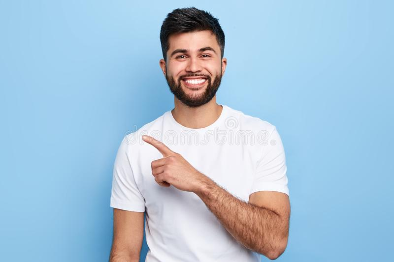 Young handsome cheerful man pointing, isolated on blue background royalty free stock image