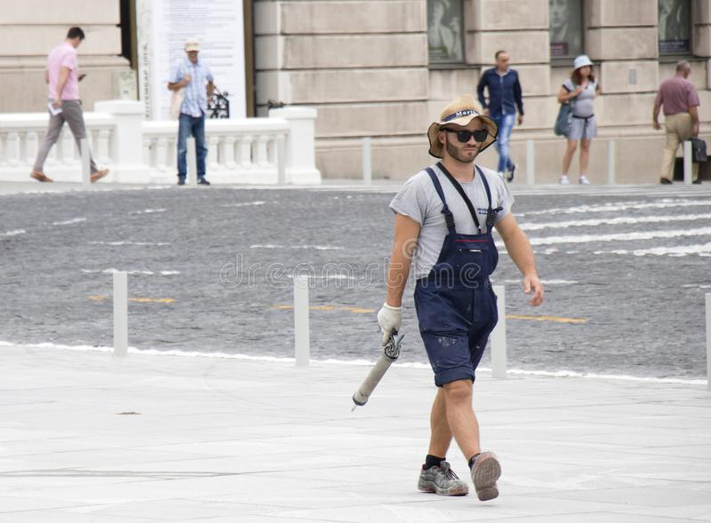 Young and handsome construction worker in casual summer outfit on city pavement holding  a caulking gun stock image