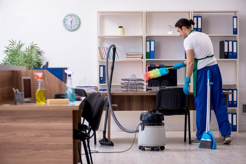 Young handsome contractor cleaning the office. The young handsome contractor cleaning the office stock photos