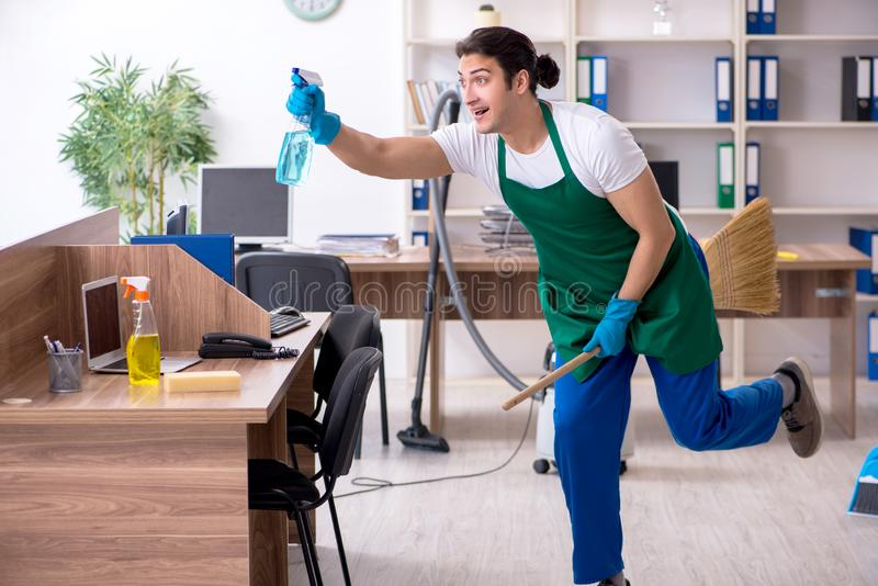 Young handsome contractor cleaning the office. The young handsome contractor cleaning the office royalty free stock photos