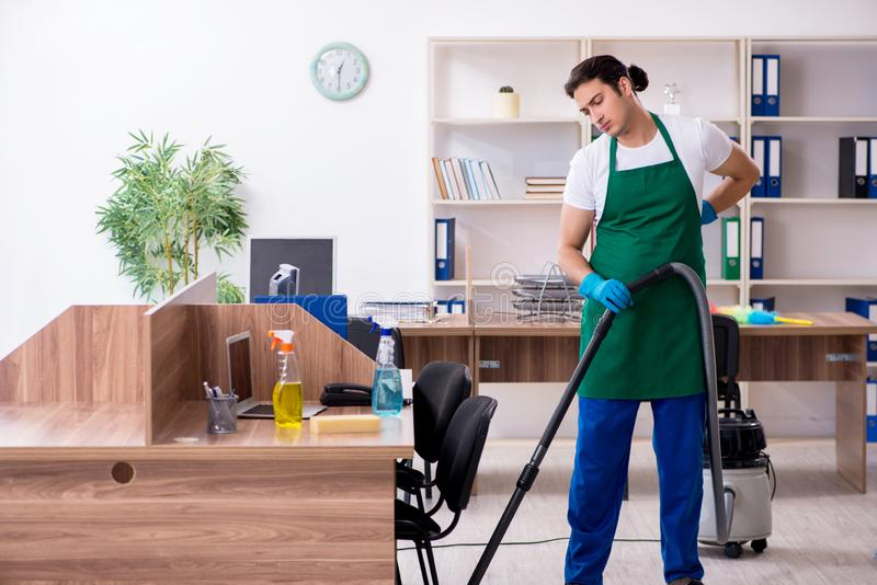 Young handsome contractor cleaning the office. The young handsome contractor cleaning the office royalty free stock photography