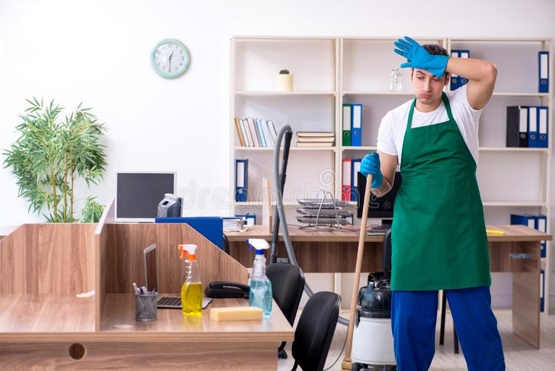 Young handsome contractor cleaning the office. The young handsome contractor cleaning the office royalty free stock images