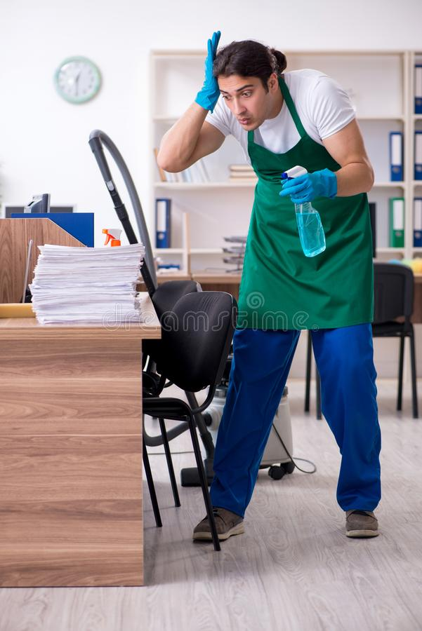 Young handsome contractor cleaning the office. The young handsome contractor cleaning the office royalty free stock photo