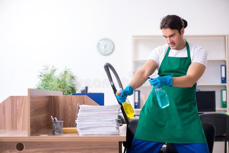 Young handsome contractor cleaning the office royalty free stock photo