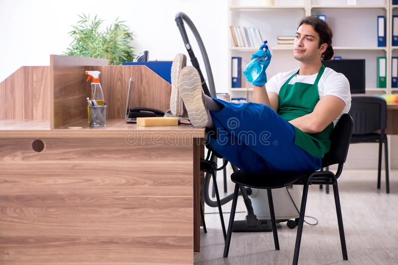 Young handsome contractor cleaning the office royalty free stock image
