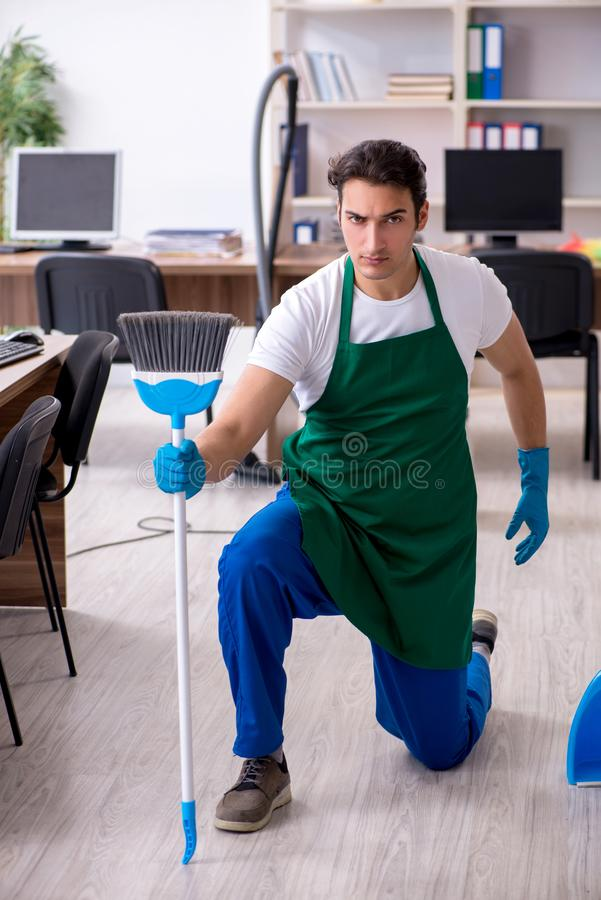 Young handsome contractor cleaning the office royalty free stock photography