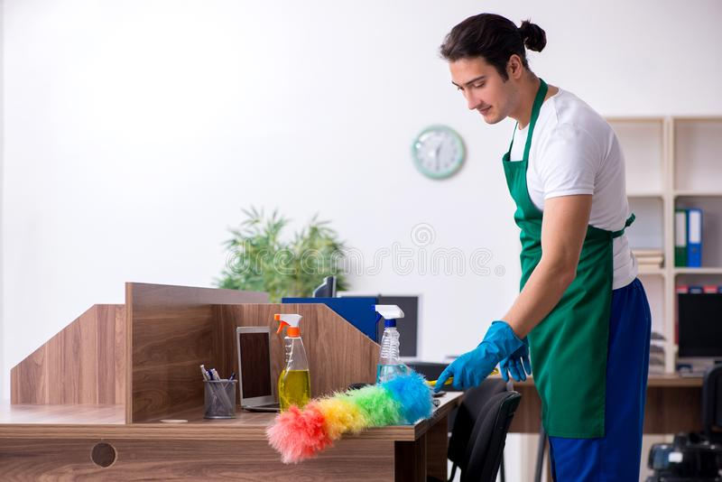 Young handsome contractor cleaning the office. The young handsome contractor cleaning the office stock photography