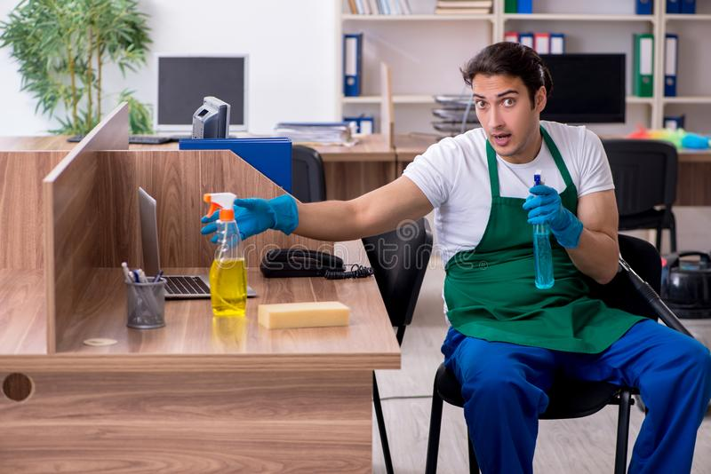 Young handsome contractor cleaning the office. The young handsome contractor cleaning the office stock photo