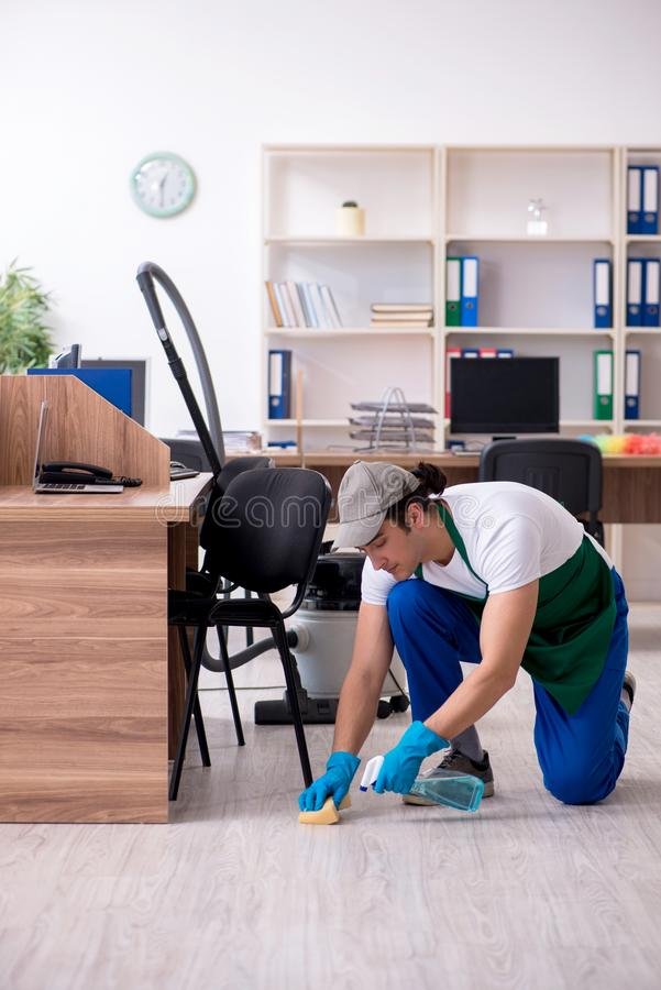 Young handsome contractor cleaning the office. The young handsome contractor cleaning the office royalty free stock image