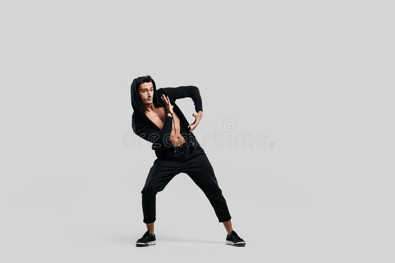 Young handsome young dancer dressed in black pants, a sweatshirt on a naked torso is dancing street dance. He makes royalty free stock images
