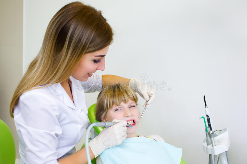 Young handsome dentist treats tooth child, a woman dentist royalty free stock image
