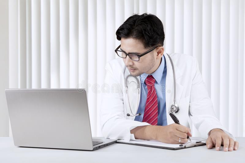 Doctor looking at his laptop while writing a prescription stock photos