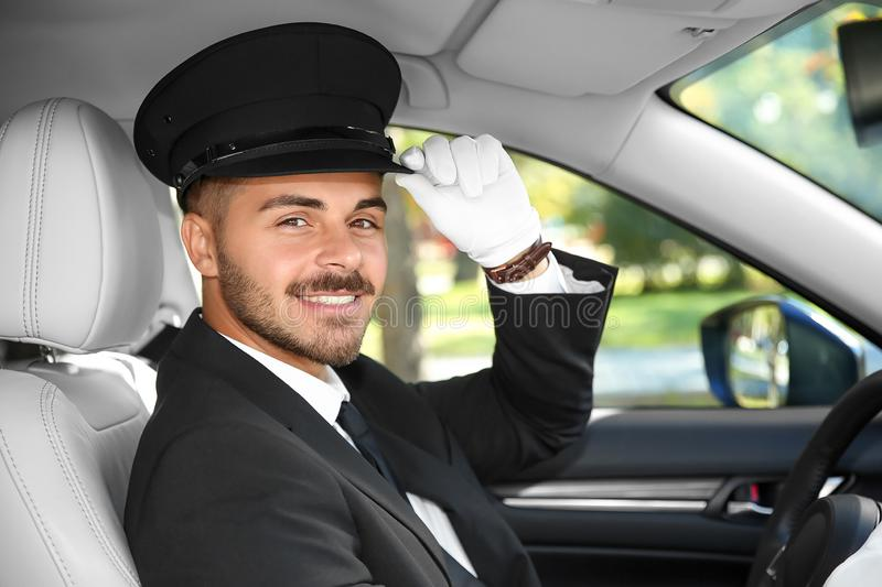 Young handsome driver in luxury car. Chauffeur service royalty free stock photo