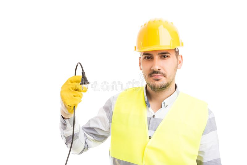 Young handsome electrician holding unplugged cable stock photos