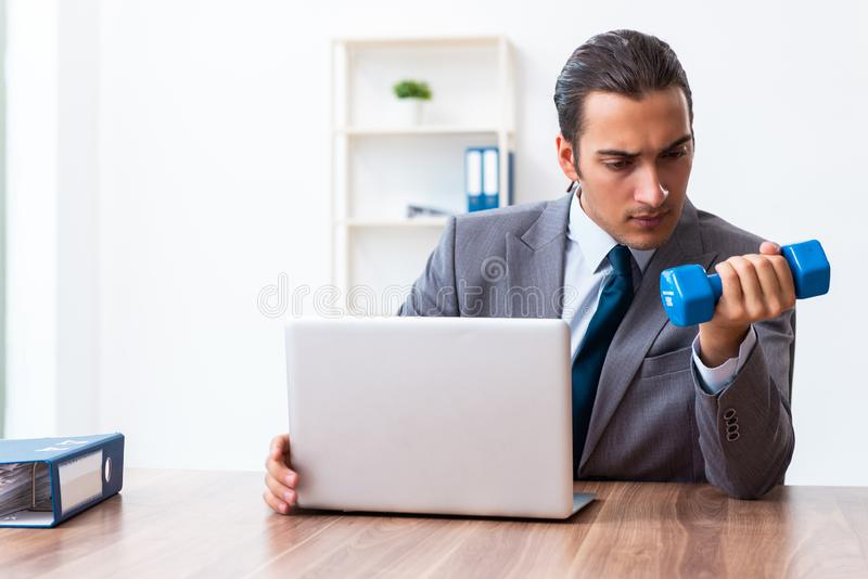 Young handsome employee doing sport exercises at workplace. The young handsome employee doing sport exercises at workplace royalty free stock image