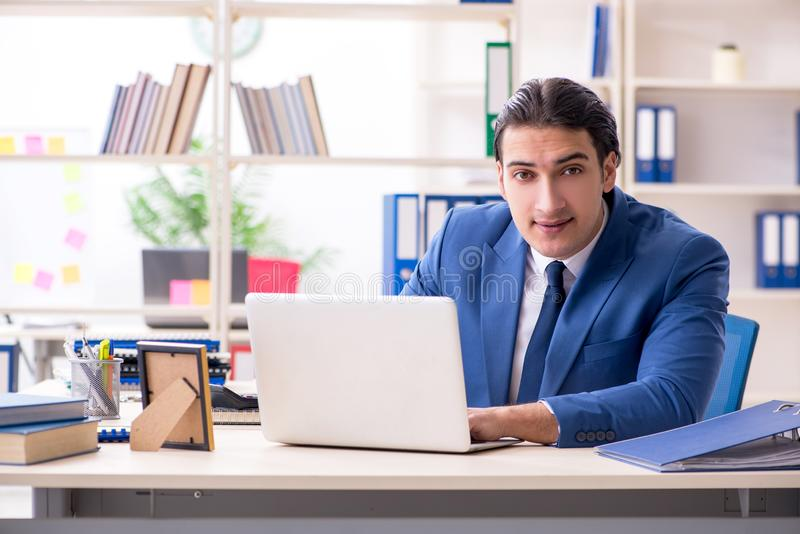 Young handsome employee in the office royalty free stock photos