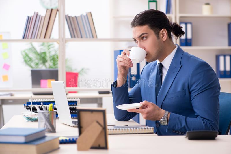 Young handsome employee in the office stock photo