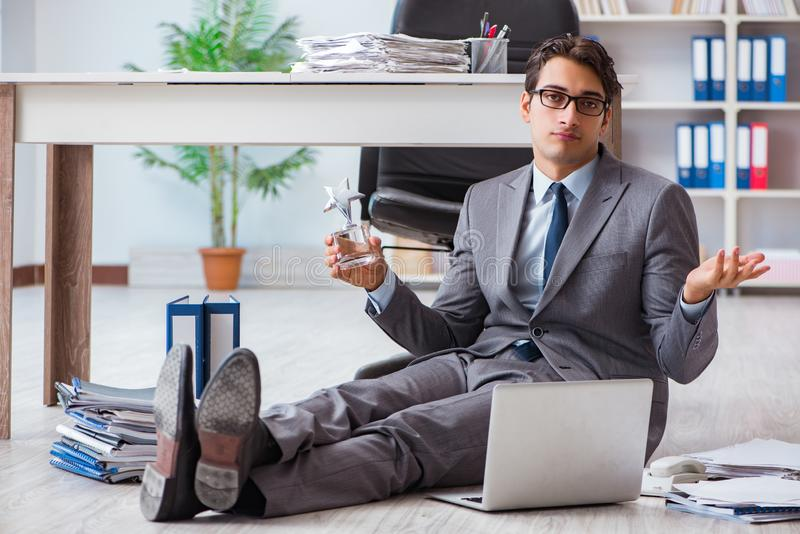 The young handsome employee sitting on the floor in the office. Young handsome employee sitting on the floor in the office royalty free stock images