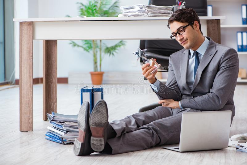 The young handsome employee sitting on the floor in the office. Young handsome employee sitting on the floor in the office stock photography