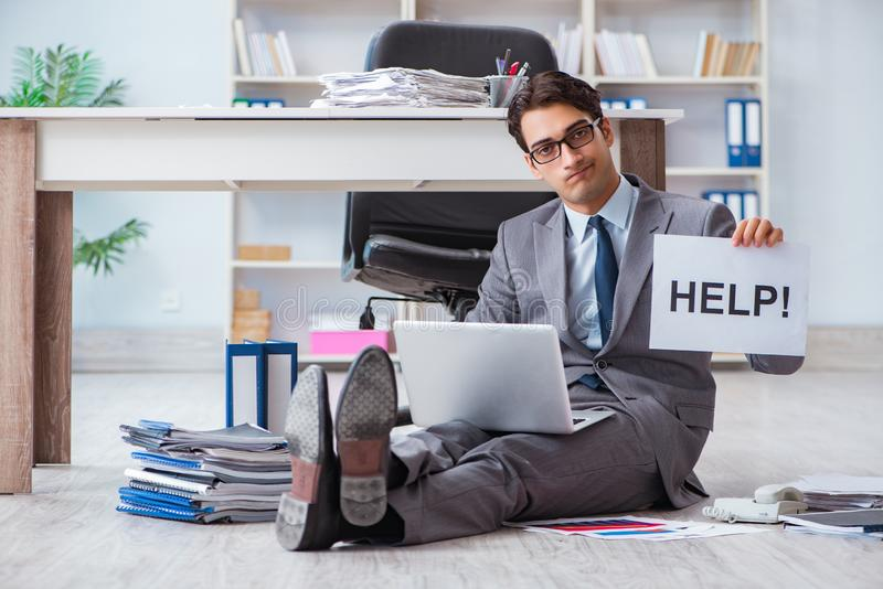 The young handsome employee sitting on the floor in the office. Young handsome employee sitting on the floor in the office royalty free stock photo