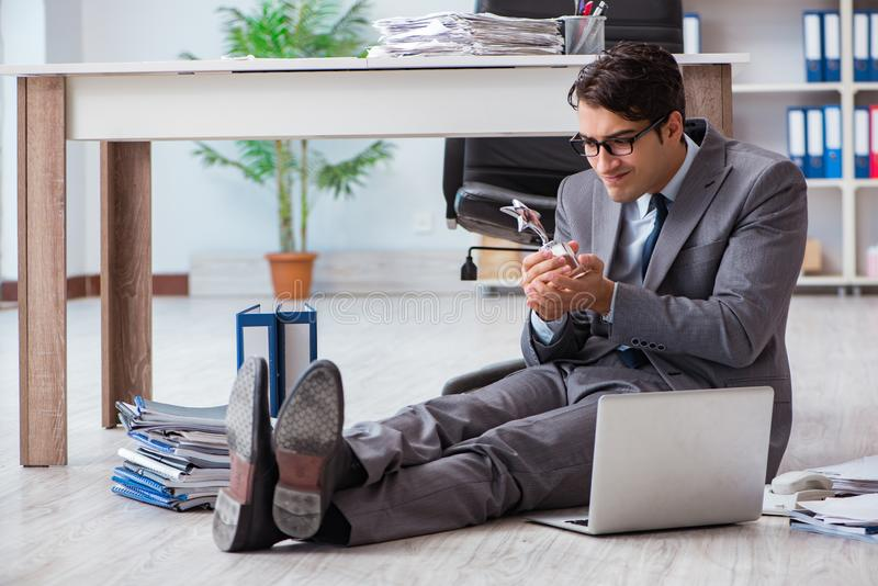 The young handsome employee sitting on the floor in the office. Young handsome employee sitting on the floor in the office stock photo