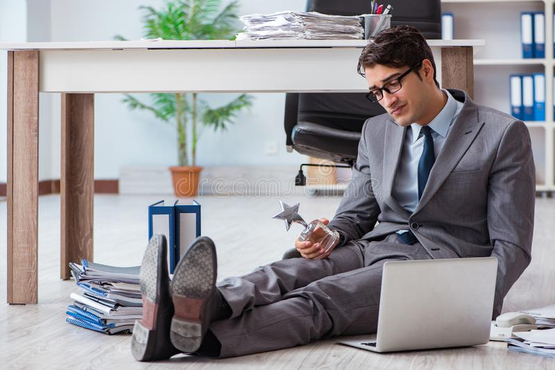 The young handsome employee sitting on the floor in the office. Young handsome employee sitting on the floor in the office stock images