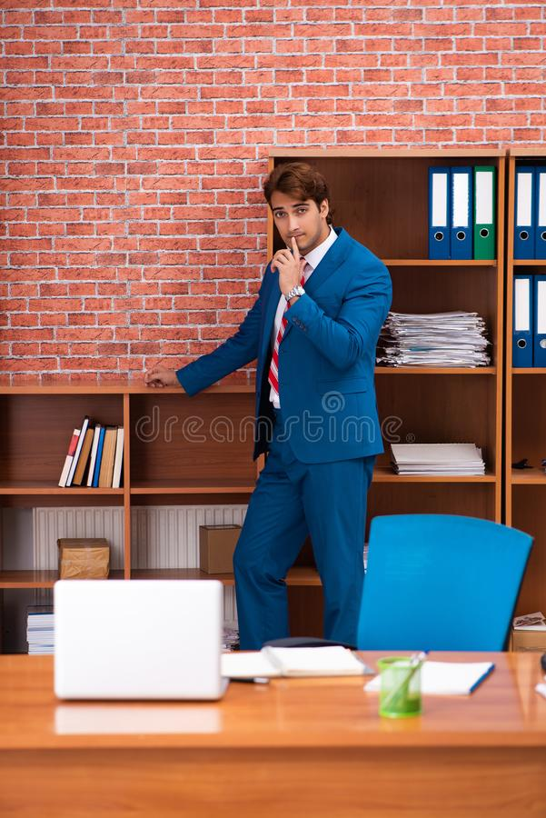 The young handsome employee sitting in the office. Young handsome employee sitting in the office royalty free stock images
