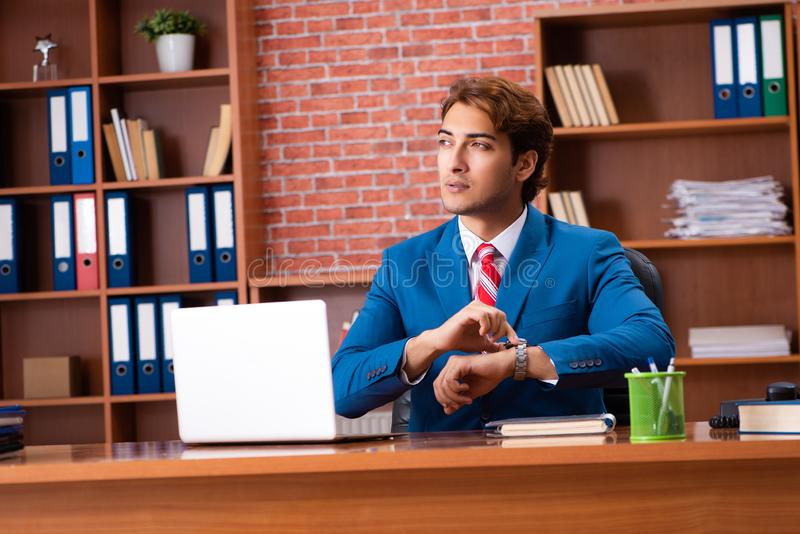 The young handsome employee sitting in the office. Young handsome employee sitting in the office royalty free stock photography
