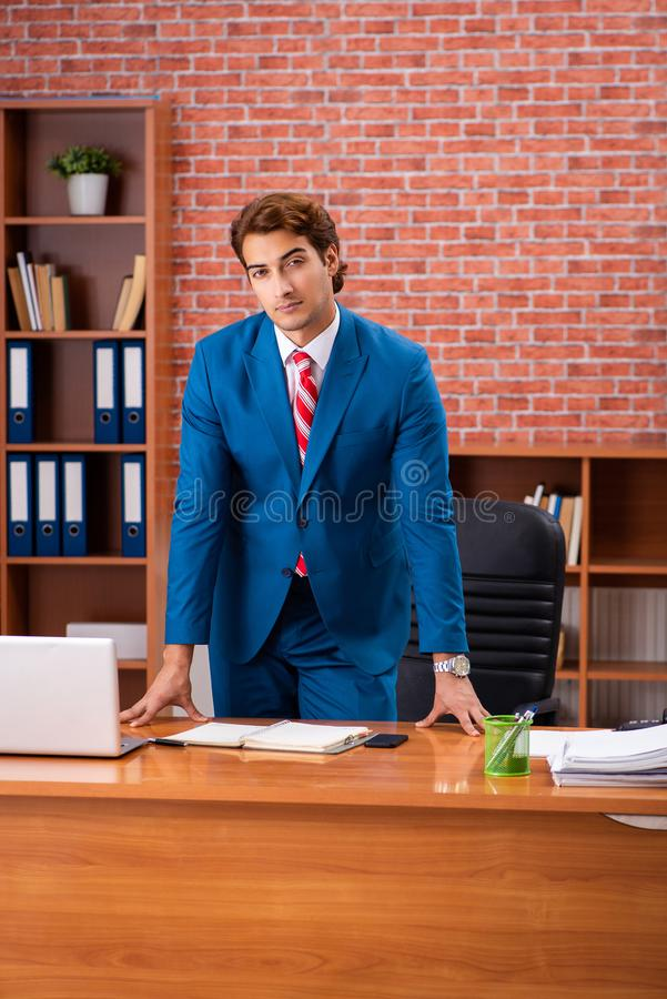 The young handsome employee sitting in the office. Young handsome employee sitting in the office stock photo