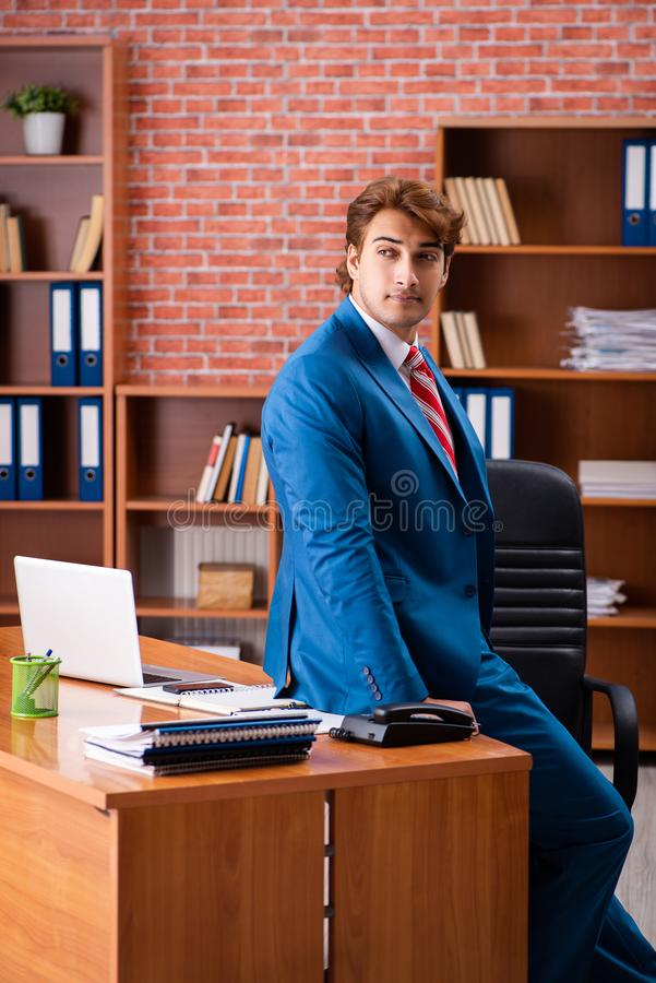 The young handsome employee sitting in the office. Young handsome employee sitting in the office royalty free stock photo