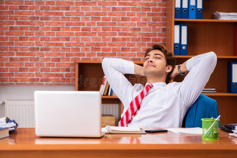 The young handsome employee sitting in the office. Young handsome employee sitting in the office stock photography