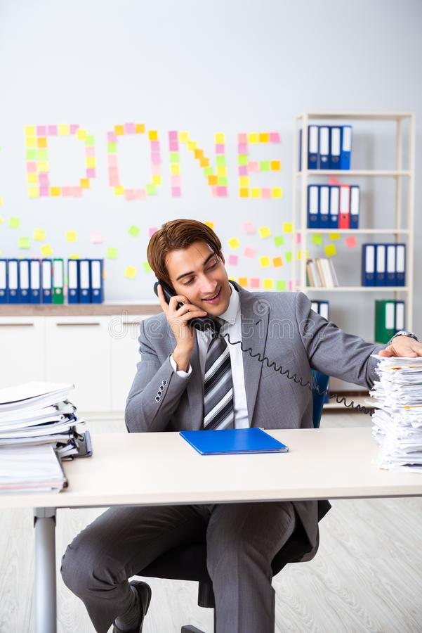 The young handsome employee sitting at the office. Young handsome employee sitting at the office royalty free stock image