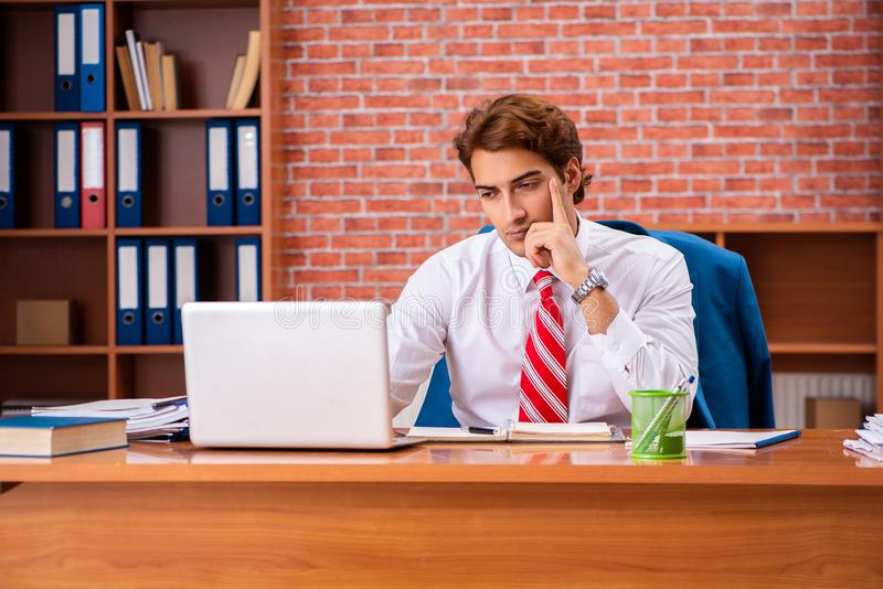 The young handsome employee sitting in the office. Young handsome employee sitting in the office royalty free stock photos